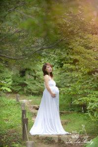 マタニティドレスを着て自然の中で撮影